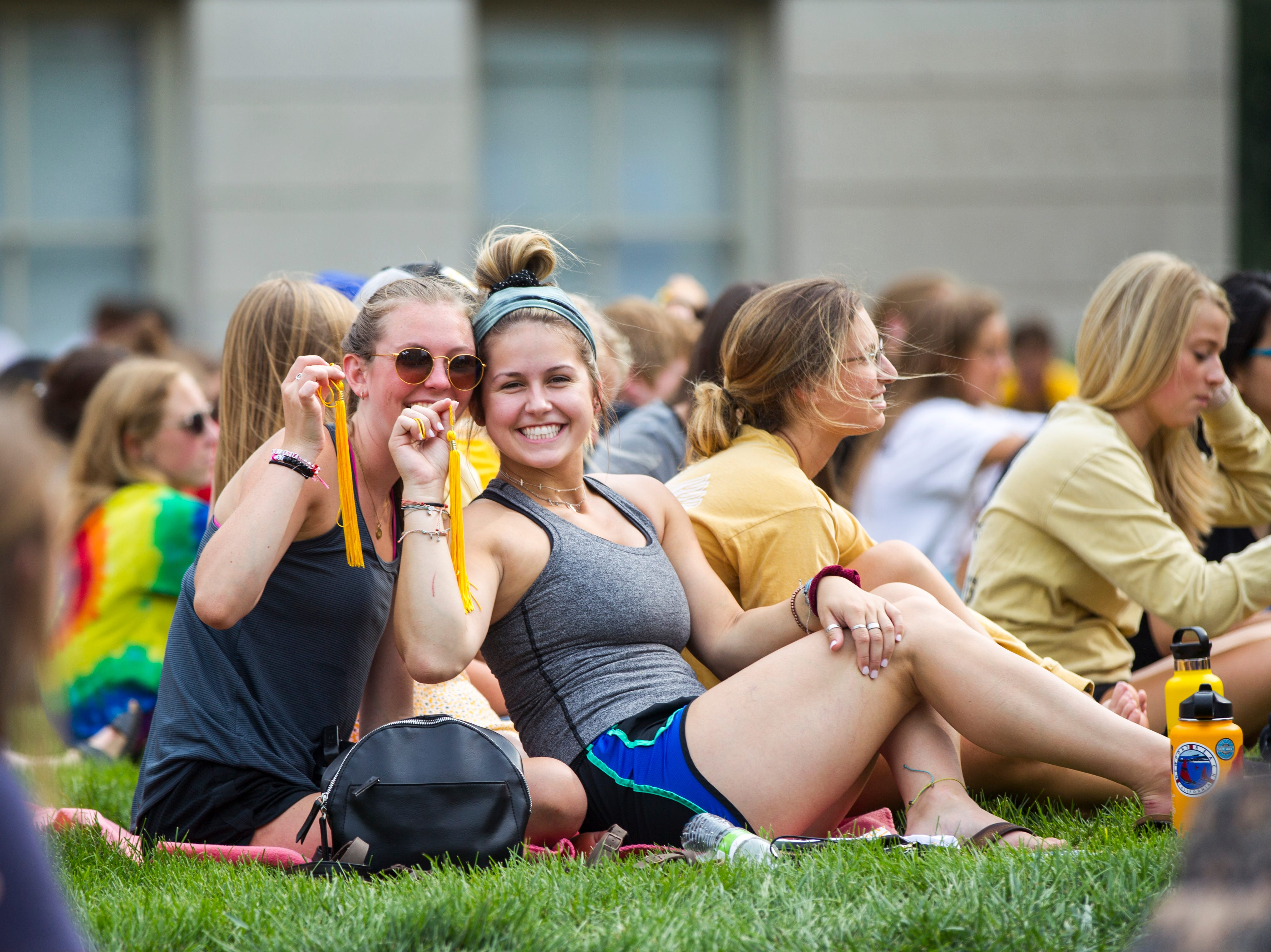 Students hold up tassels during the University of Iowa class of 2022 convocation on Sunday, Aug. 19, 2018, at the Pentacrest in Iowa City.