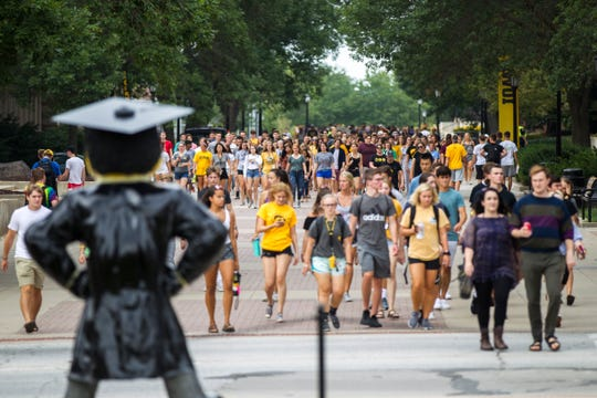 Students walk along the T. Anne Cleary Walkway during the University of Iowa class of 2022 convocation on Sunday, Aug. 19, 2018, at the Pentacrest in Iowa City.