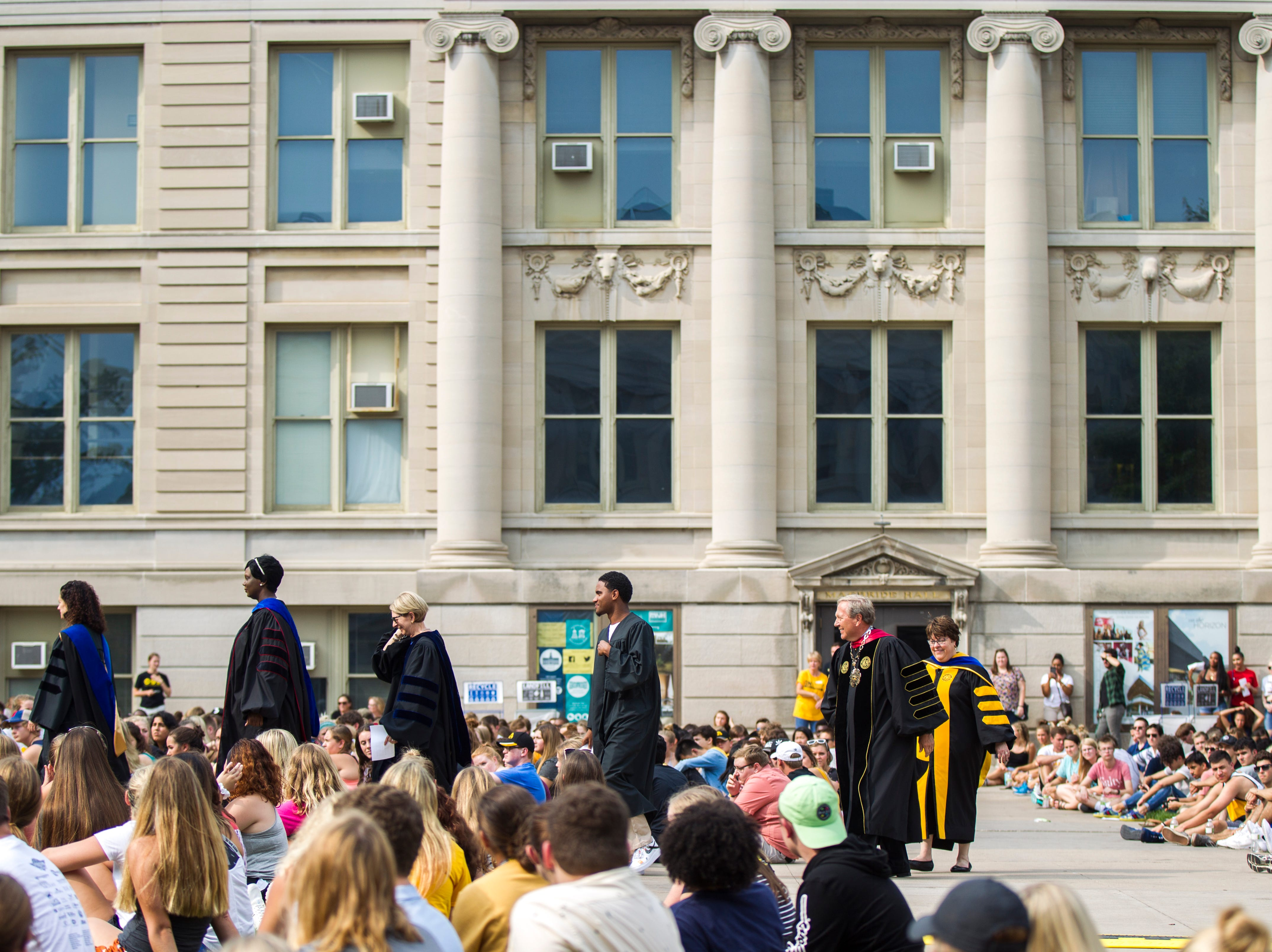 Melissa Shivers, (second from left) Sue Curry, Darius Christiansen, and Bruce Harreld walk towards a stage during the University of Iowa class of 2022 convocation on Sunday, Aug. 19, 2018, at the Pentacrest in Iowa City.