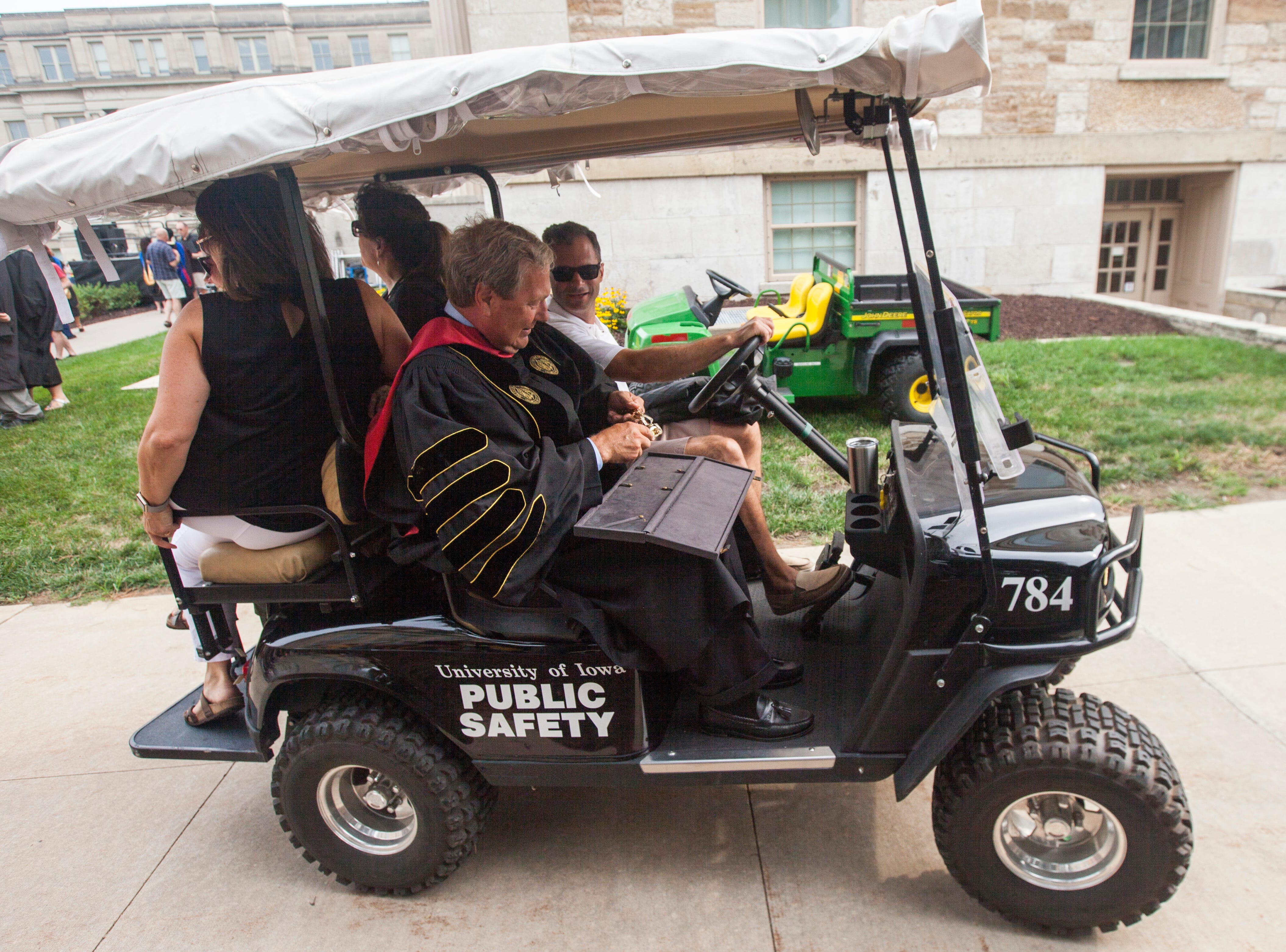 "University of Iowa President J. Bruce Harreld gets a ride in the ""Kieth-mobile"" after speaking during the University of Iowa class of 2022 convocation on Sunday, Aug. 19, 2018, at the Pentacrest in Iowa City."