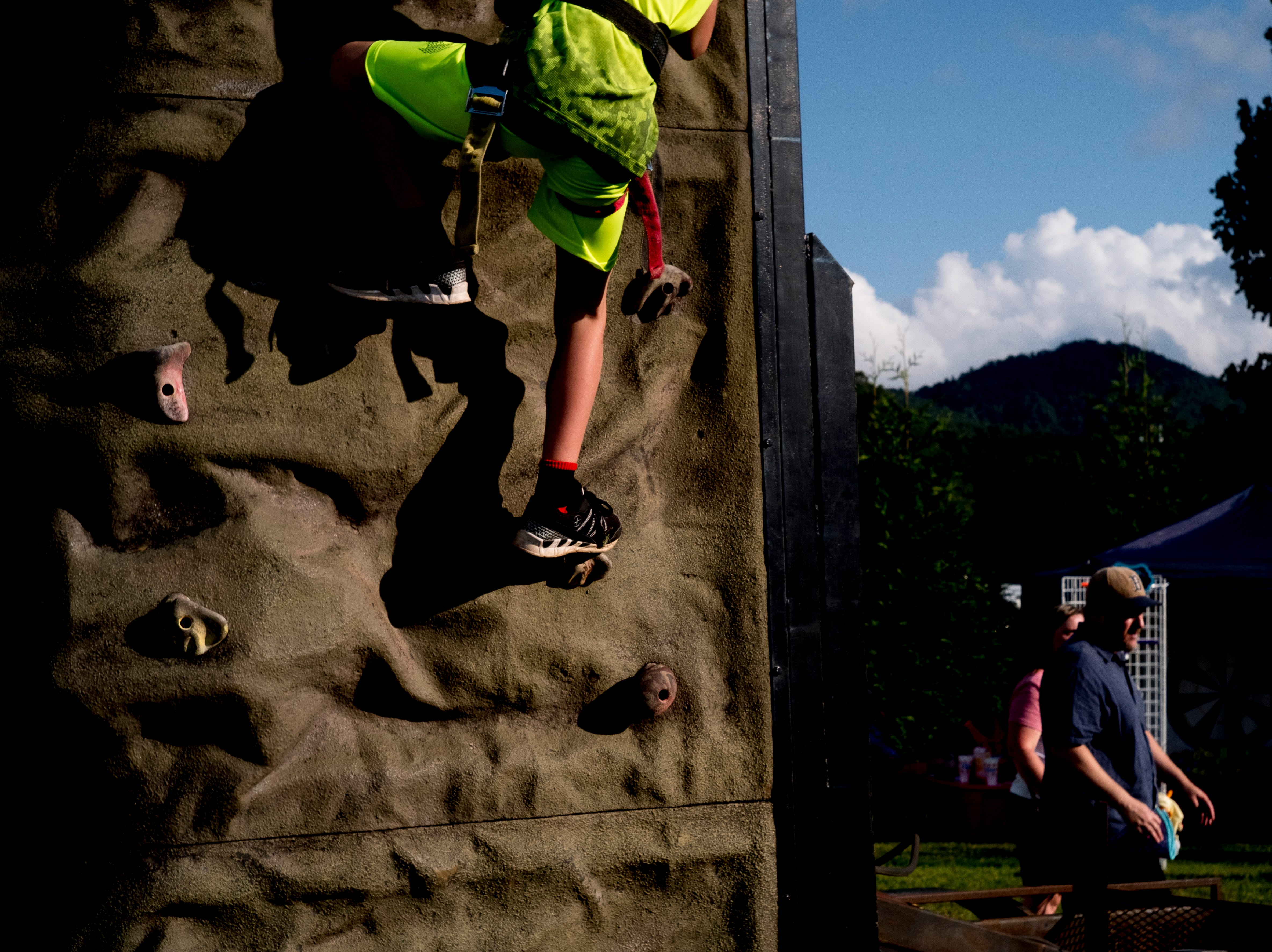 A kid climbs a rock wall at the second annual Smoky Mountain Balloon Festival in Townsend, Tennessee on Saturday, August 18, 2018. The festival featured several hot air balloons, food trucks, wine tasting and live entertainment.