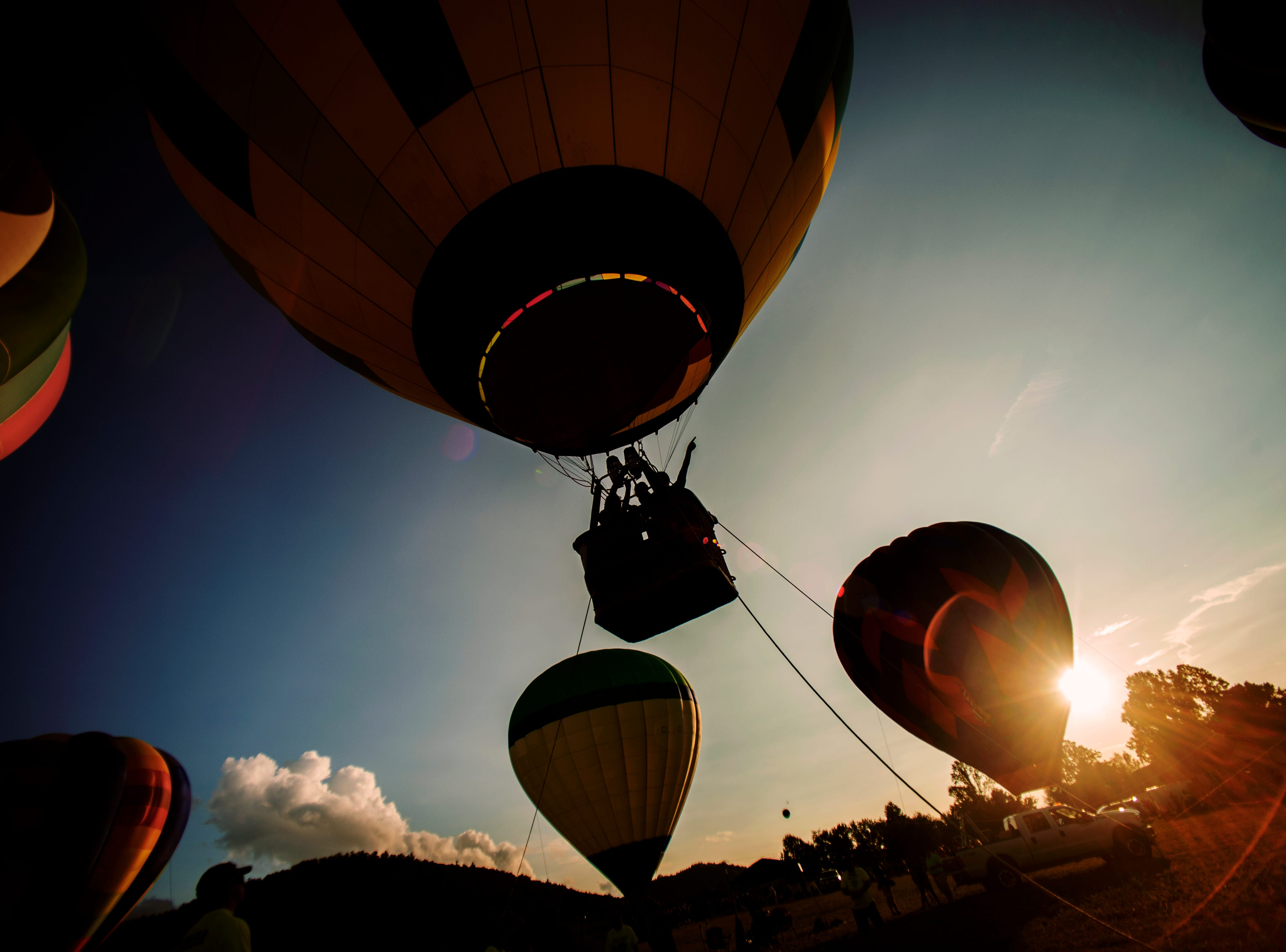 A balloon rider points from the basket at the second annual Smoky Mountain Balloon Festival in Townsend, Tennessee on Saturday, August 18, 2018. The festival featured several hot air balloons, food trucks, wine tasting and live entertainment.