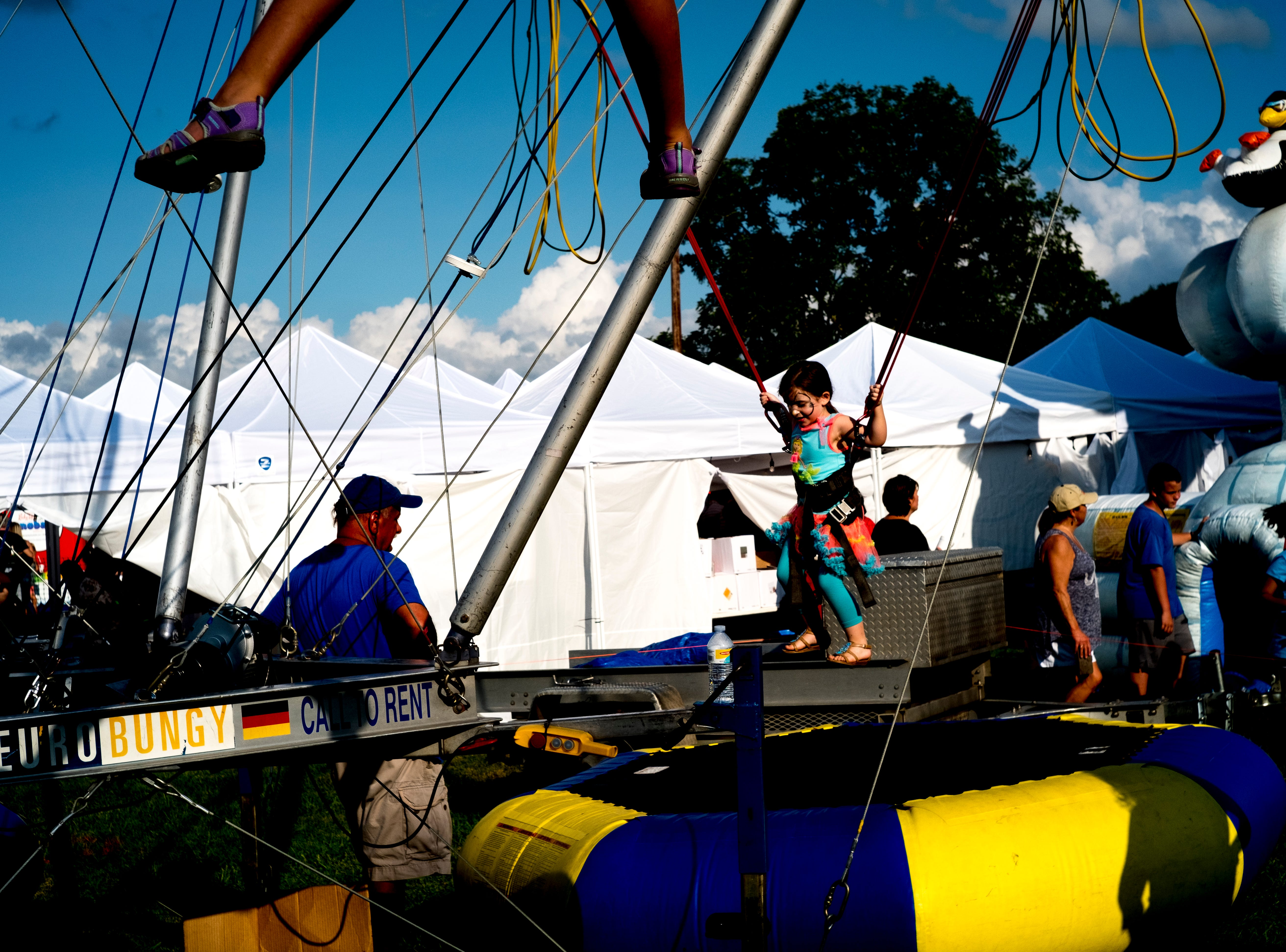 Kids play on a trampoline at the second annual Smoky Mountain Balloon Festival in Townsend, Tennessee on Saturday, August 18, 2018. The festival featured several hot air balloons, food trucks, wine tasting and live entertainment.
