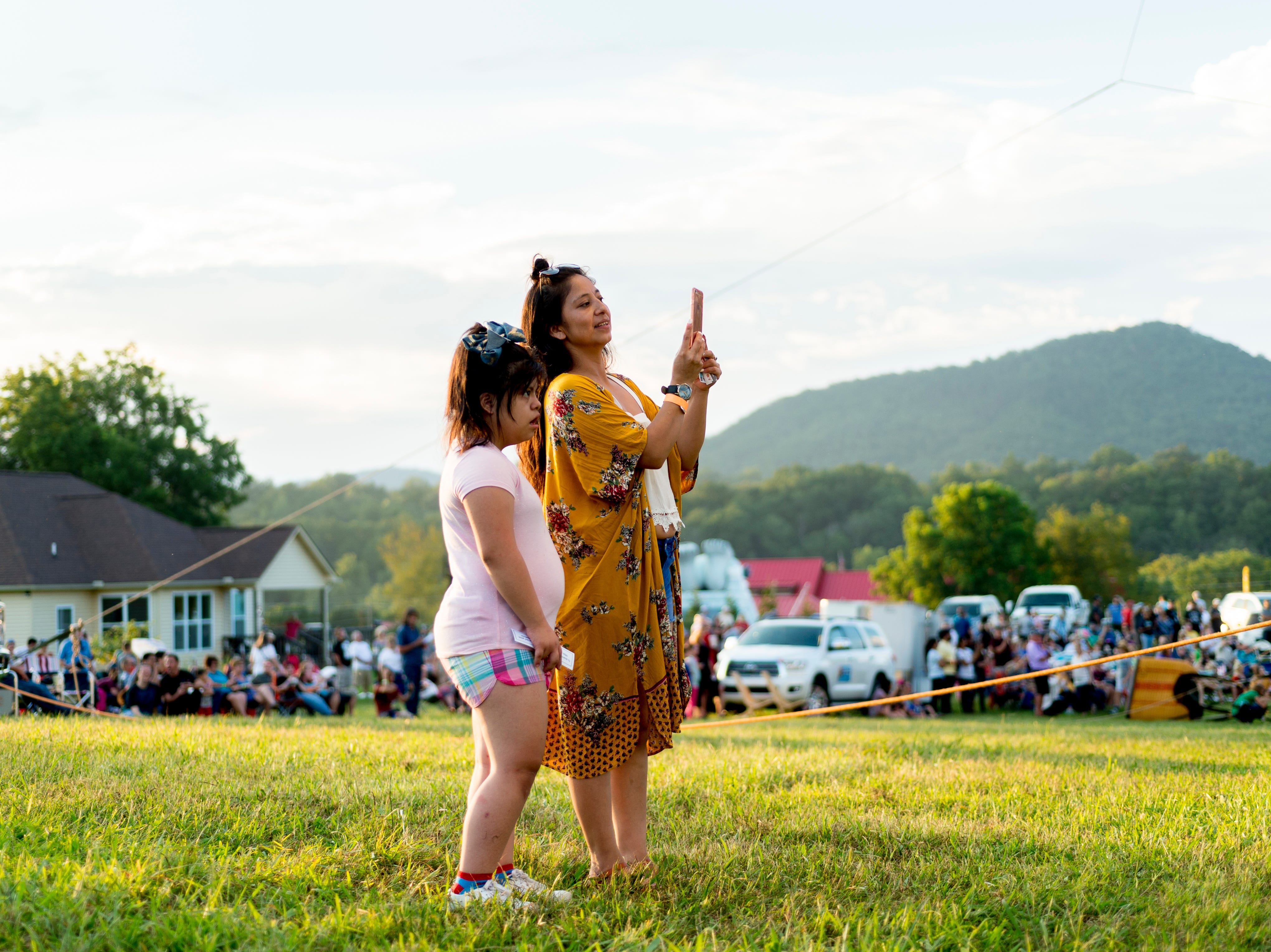 Elena Velasquez, of Chattanooga, and Ashley Velasquez snap a photo of the hot air balloons at the second annual Smoky Mountain Balloon Festival in Townsend, Tennessee on Saturday, August 18, 2018. The festival featured several hot air balloons, food trucks, wine tasting and live entertainment.