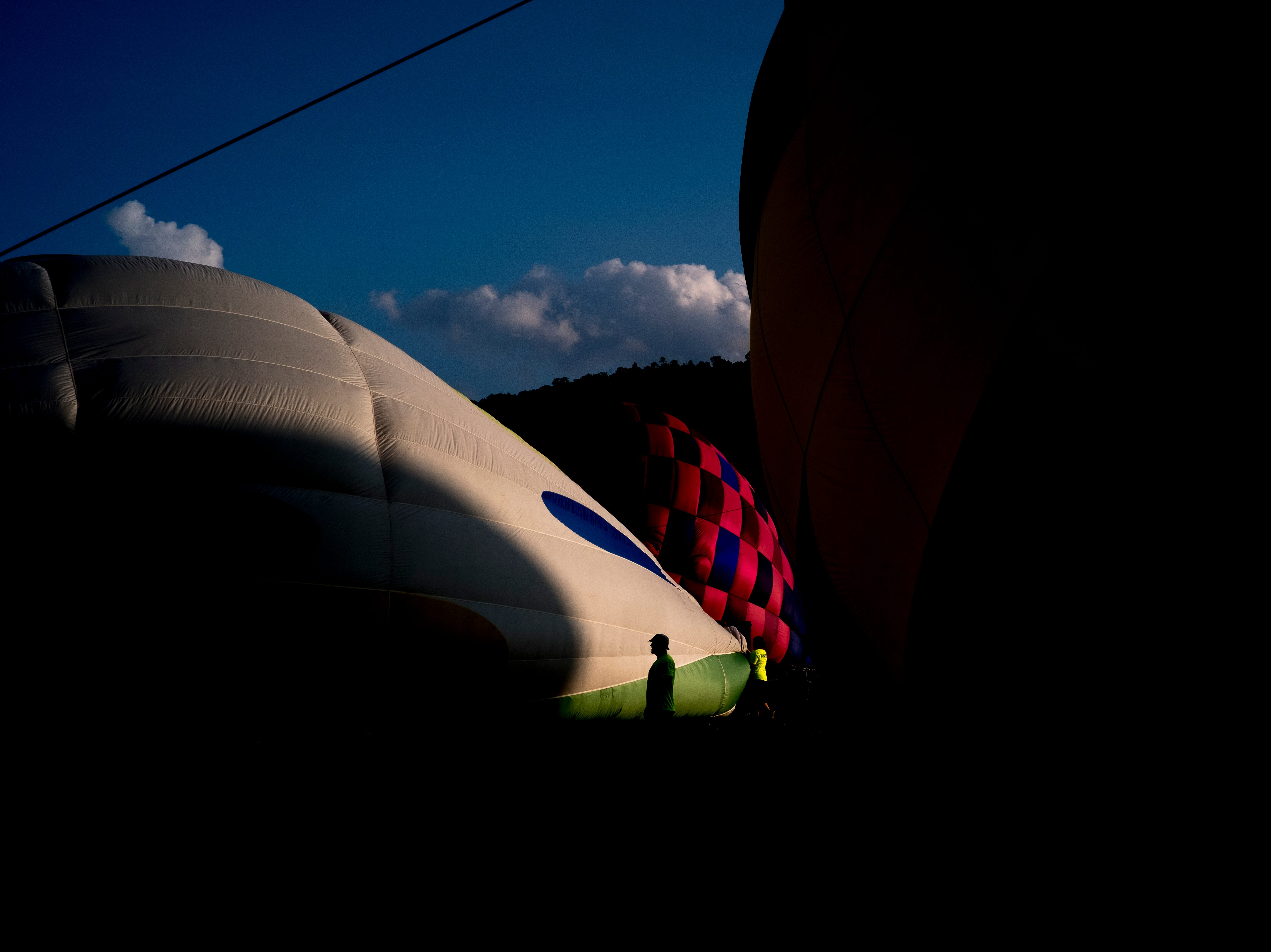 A worker passes by an inflating hot air balloon at the second annual Smoky Mountain Balloon Festival in Townsend, Tennessee on Saturday, August 18, 2018. The festival featured several hot air balloons, food trucks, wine tasting and live entertainment.
