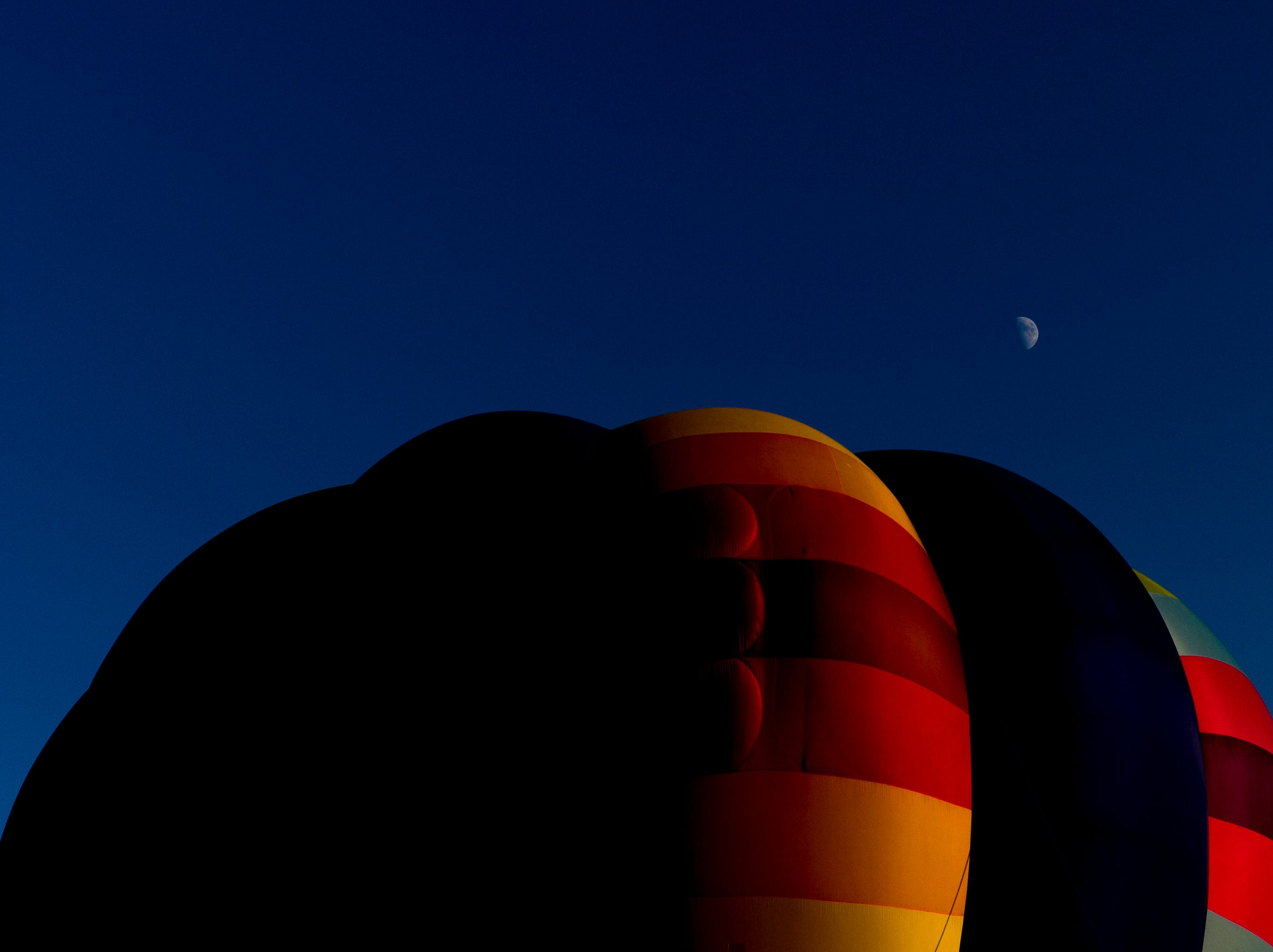 The moon can be seen rising above a hot air balloon at the second annual Smoky Mountain Balloon Festival in Townsend, Tennessee on Saturday, August 18, 2018. The festival featured several hot air balloons, food trucks, wine tasting and live entertainment.