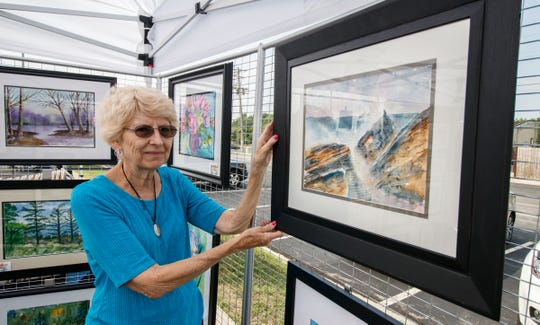 Kathy David of Franklin hangs artwork in her booth during the Celebration of Greenfield Arts outdoor art fair at the Greenfield Public Library on Saturday, August 18, 2018. The event raised funds for the library to commission art for the atrium and children's reading corner.
