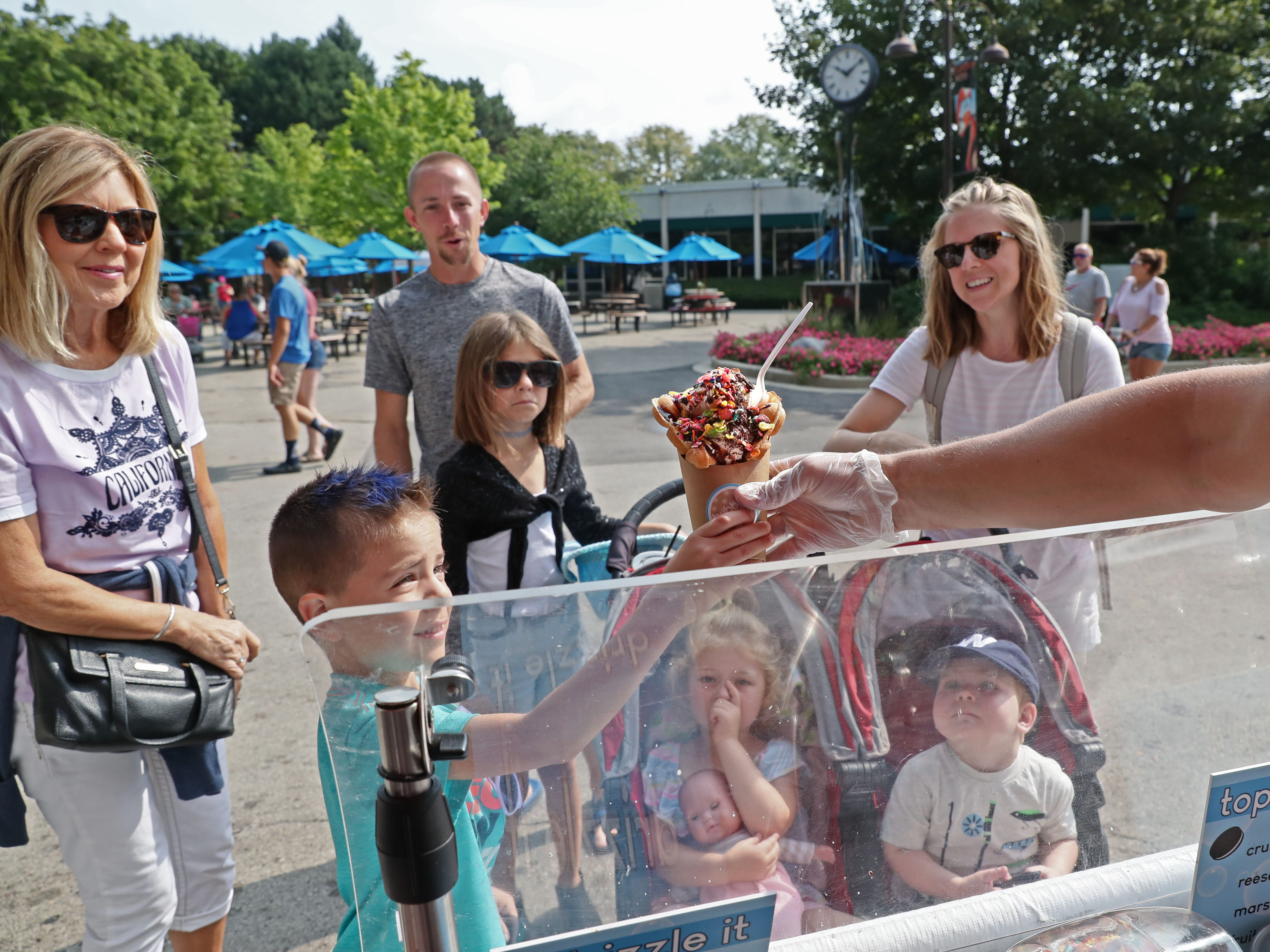 Marcus Hansen, 6, of Oconomowoc is handed a bubble waffle from Bubble Waffle Shoppes as the rest of the family looks on in envy.  From left are his great-grandmother, Vicki Smith of Watertown, father, Terry Hansen, sister Melanie Hansen, 8, aunt, Nicole Deklotz of Hales Corners, and her two children, Ruthie Deklotz, 4, and Will Deklotz, 2.