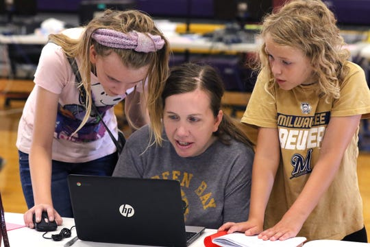 Fifth grader Grace Johnson (left) and Third Grader Sophia Johnson work with their mother Corinne Johnson to enter information during Registration Day for all Cudahy district students at Cudahy High School on Aug. 16.