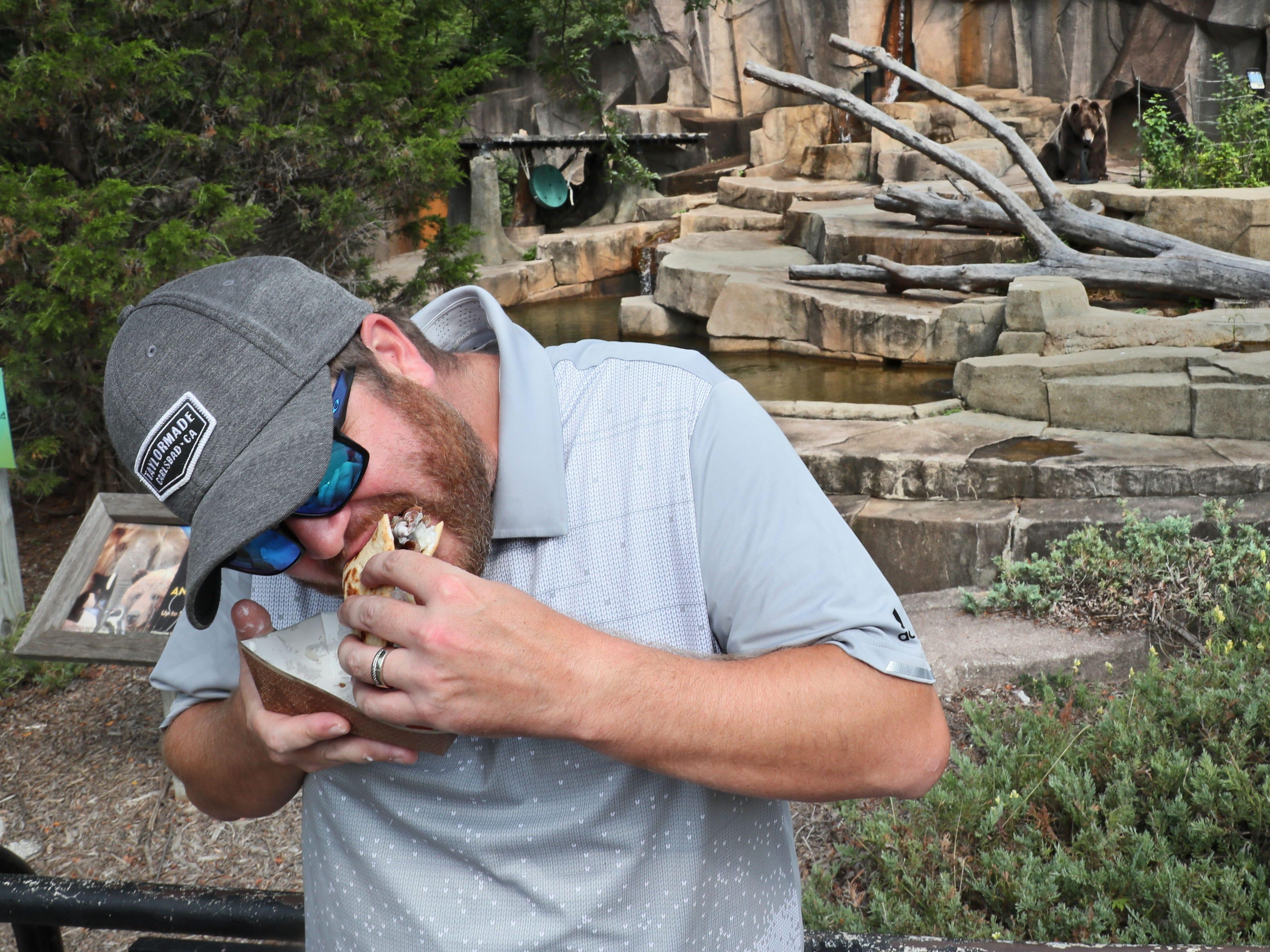 Rob Borden of Johnson Creek eats a gyro sandwich from Aladdin while brown bear Boris at rear right looks on.