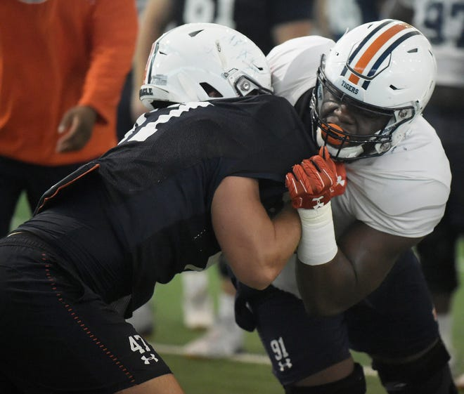 Auburn defensive end Nick Coe (right) tries to get around a block set by tight end John Samuel Shenker during practice on Saturday, Aug. 18, 2018 in Auburn, Ala.