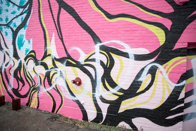 Spray paint graffiti from one end to the other of the mural along the Mark III Tap Room in downtown Muncie was vandalized Tuesday night.