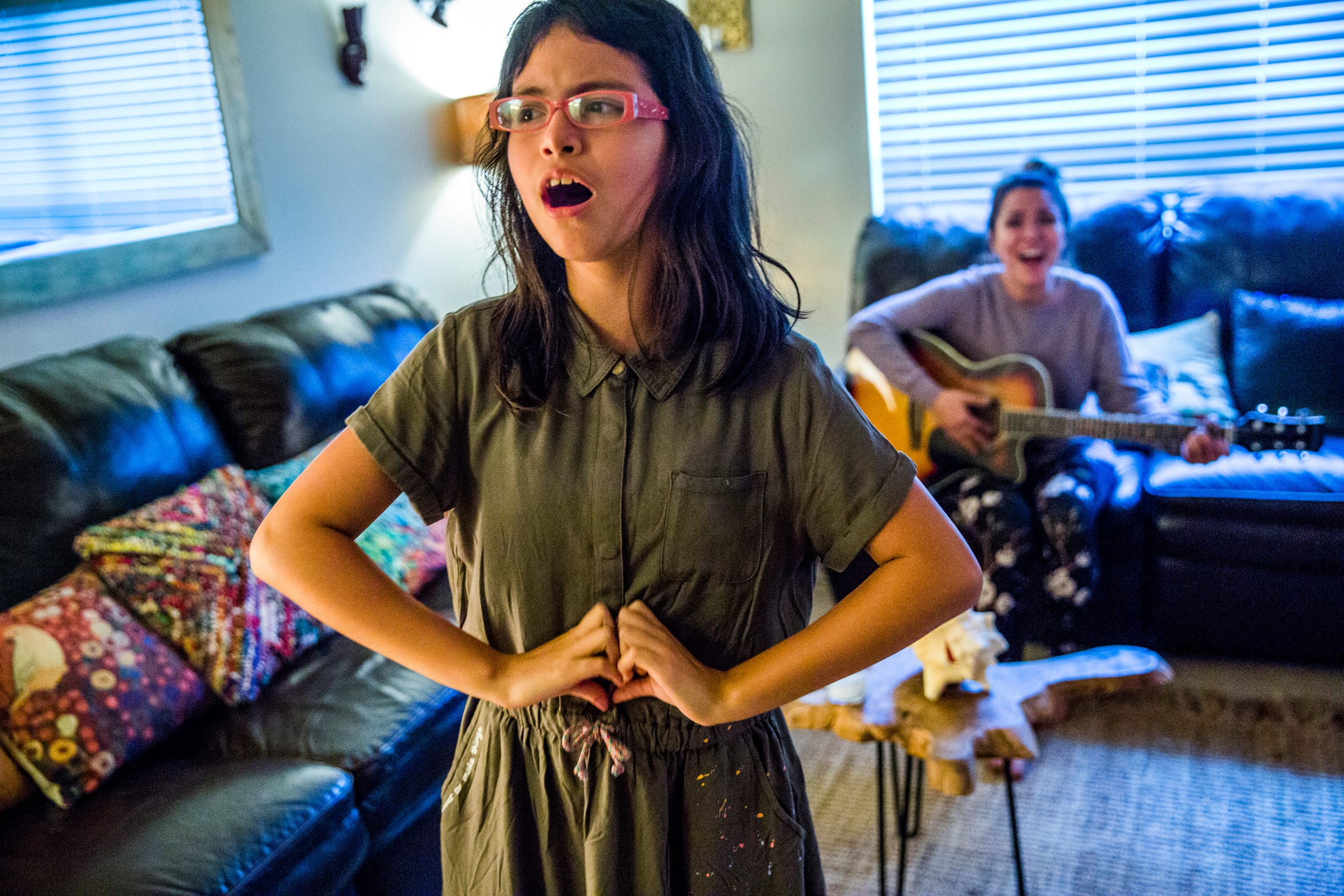 """Camila Chang, 11, sings while her mother, Marcela Guimoye, plays guitar in their North Naples home on Tuesday, Aug. 14, 2018. Music is an integral part of their life together as mother and daughter. Guimoye takes many practices from EndlessBrain and incorporates them into Camila's life at home, and vice versa. """"She's my best friend. Everything I like to do, she likes to do too,"""" Guimoye says."""
