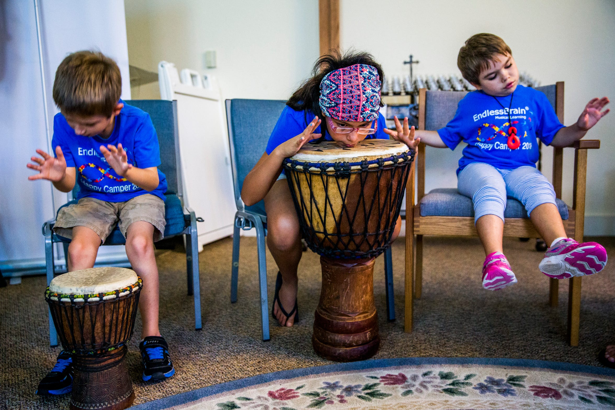 """Nicholaj Solovjov, 7, from left, Camila Chang, 11, and Talley Louise Wilson, 7, sing and drum together during the EndlessBrain summer camp at Emmanuel Lutheran Church in Naples on Thursday, Aug. 9, 2018. Marcela Guimoye started EndlessBrain because she felt there weren't enough resources for kids with autism. She says EndlessBrain is not musical therapy, but a place for kids with special needs to explore their musical interest. """"This EndlessBrain thing, I wake up so happy. Happy that they can feel their music,"""" Guimoye says."""