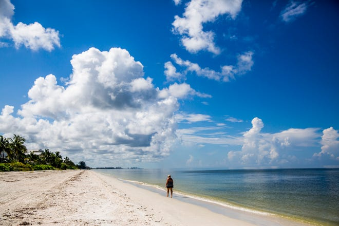 A woman walks along an empty Bonita Beach on Sunday, Aug. 19, 2018. Red tide still has a heavy presence along Collier and South Lee beaches.