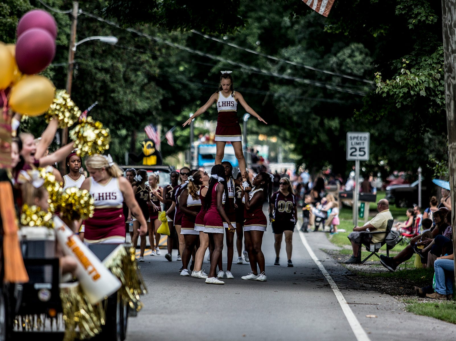 Licking Heights cheerleaders make their way down the parade route as hundred of people cheer them on.