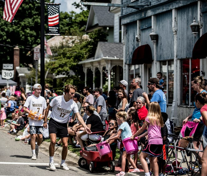 Athletes from Watkins pass out candy to youngsters during the Pataskala street parade Saturday.