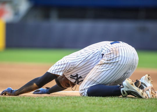 New York Yankees shortstop Didi Gregorius (18) falls to the ground after a collision at first base against the Toronto Blue Jays at Yankee Stadium.