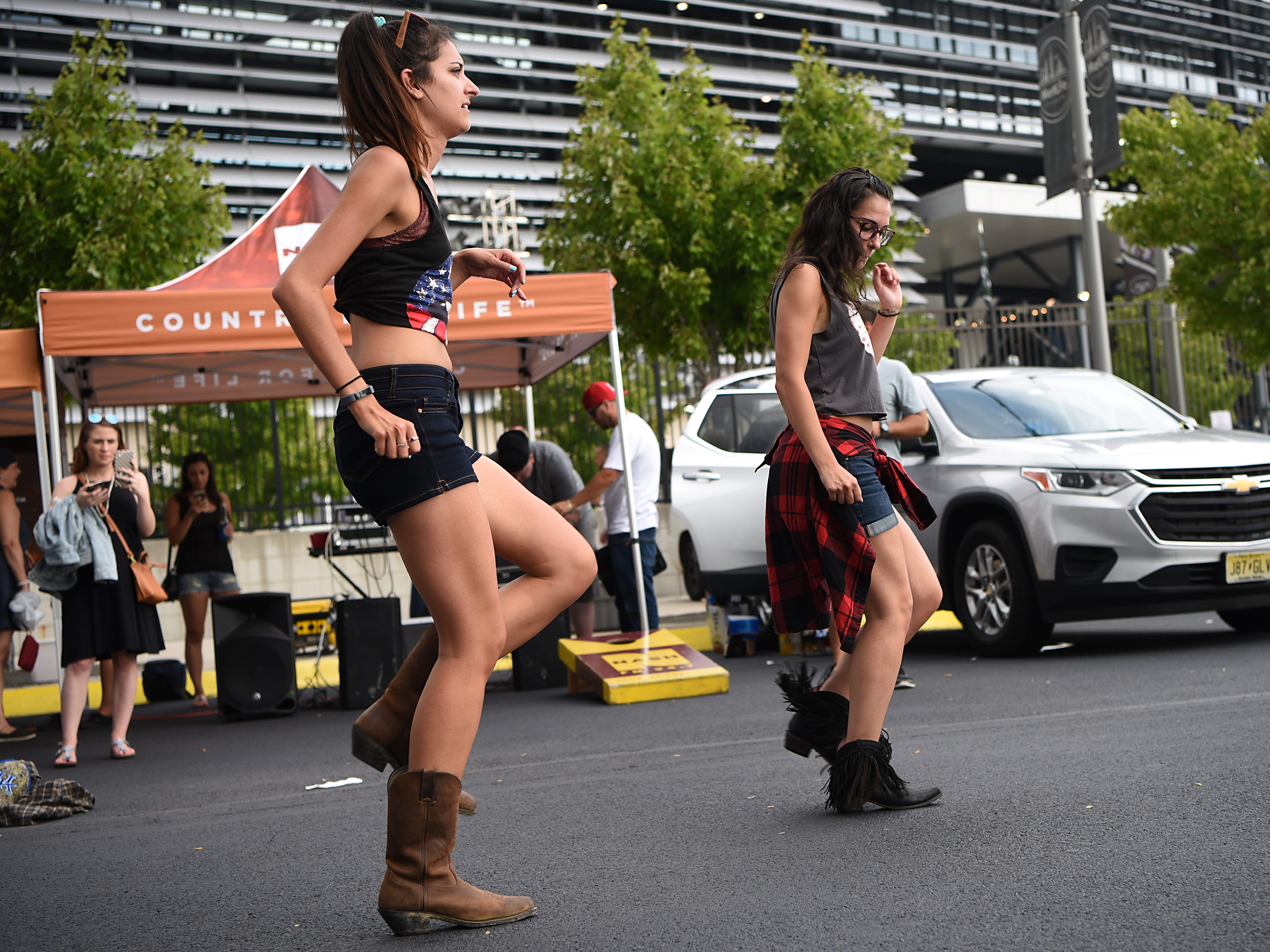Sisters Jenn Mulé and Christine Mulé from Wantagh, NY line dance in the parking lot prior to the Kenny Chesney concert at MetLife stadium in East Rutherford on Saturday August 18, 2018.