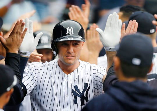 New York Yankees' Greg Bird celebrates in the dugout after hitting a grand slam in the first inning of a baseball game against the Toronto Blue Jays, Sunday, Aug. 19, 2018, in New York.