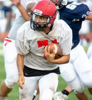 Centennial's Gabe Acosta looks for running room in a scrimmage against Silver Thursday night at the Field of Dreams.