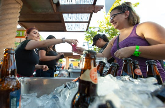 Karen Martinez, left, serves Rachel Larkin a sample of beer during the 2018 Las Cruces Summer Beer Festival and Salsa Fest at Plaza de Las Cruces on Saturday, August 18, 2018.
