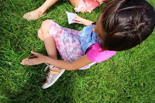 A girl waits for a Monarch butterfly to fly away and feed at the Ruidoso Hospice Foundation Butterfly Release.