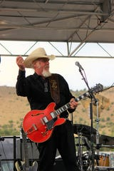 Ray Benson, founder of the Band Asleep at the Wheel, plays his guitar while performing the ever popular song 'Route 66' during a MEGA fund raiser at Glencoe Distillery July 29.