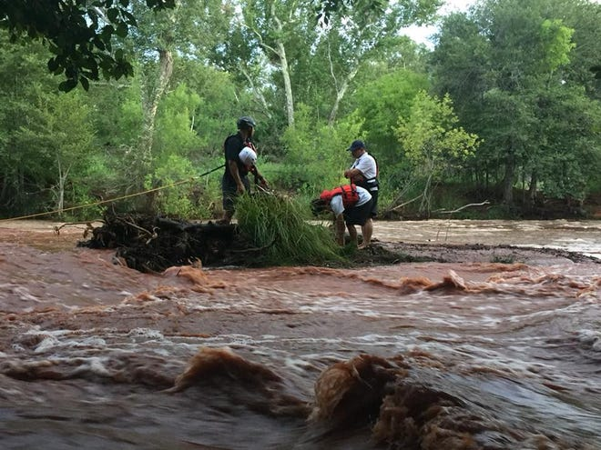 Sedona firefighters rescue three people stranded on an island in the middle of Oak Creek at the Crescent Moon Ranch State Park on Aug. 18, 2018.