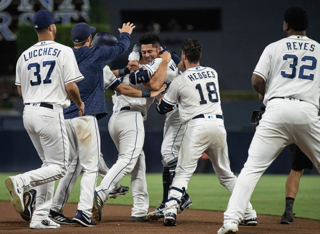 San Diego Padres celebrate after Christian Villanueva, center right, hit a walk-off single against the Arizona Diamondbacks during a baseball game in San Diego, Saturday, Aug. 18, 2018. The Padres won 7-6.