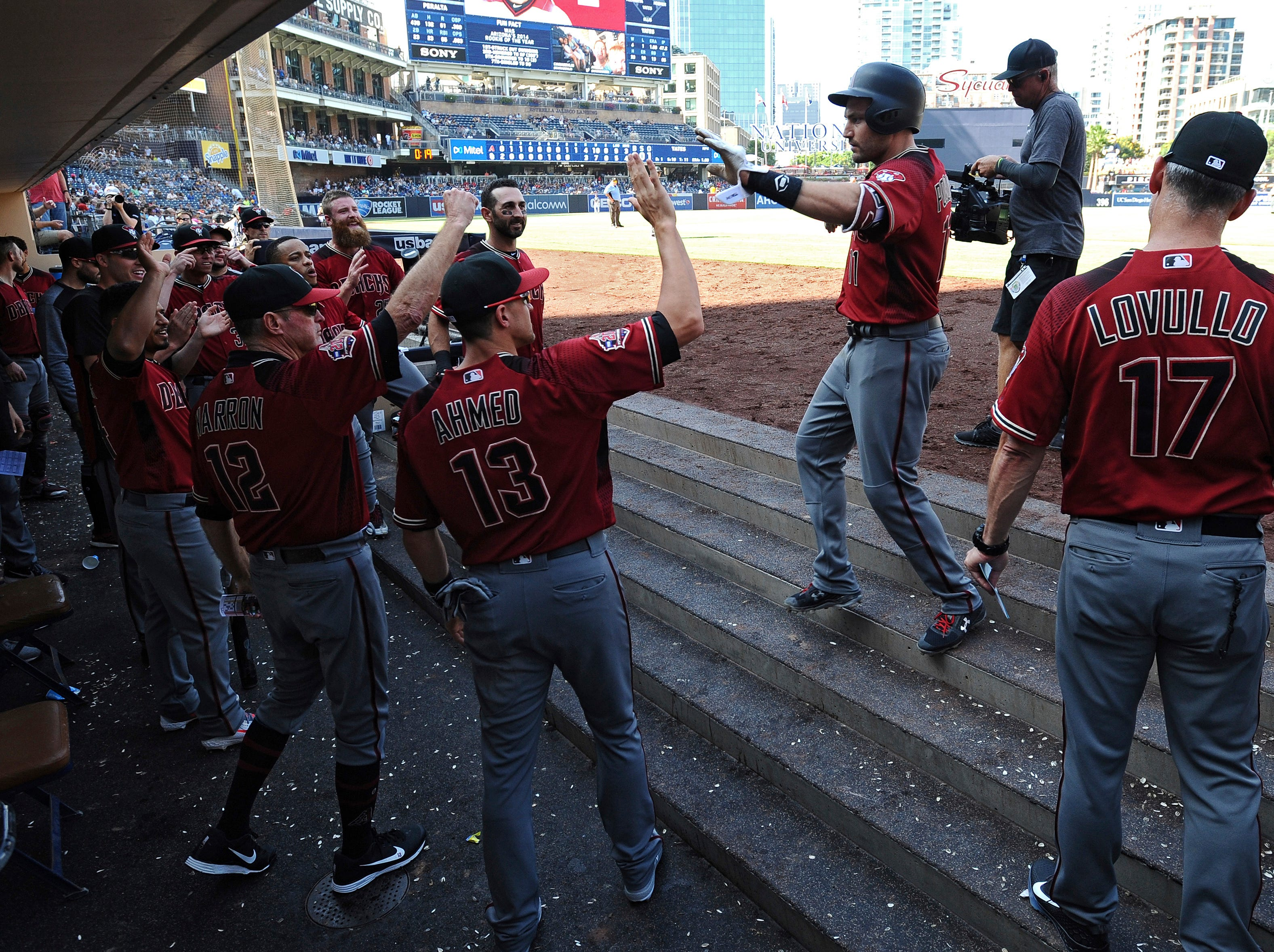 Arizona Diamondbacks center fielder A.J. Pollock, top, is congratulated in the dugout after hitting a home run during the ninth inning of a baseball game against the San Diego Padres, Sunday, Aug. 19, 2018, in San Diego.