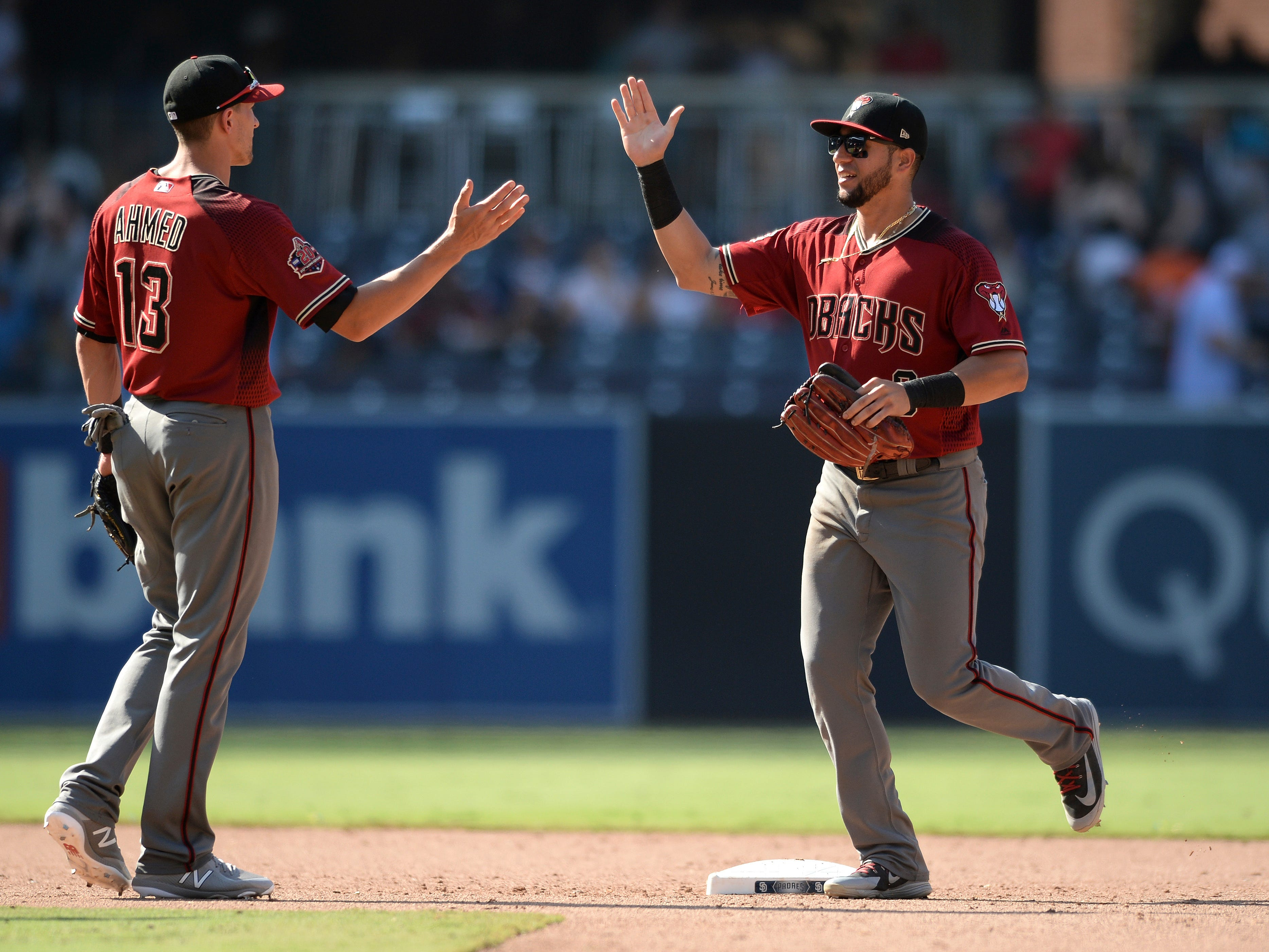 Arizona Diamondbacks' Nick Ahmed, left, and David Peralta celebrate after recording the last out of the baseball game against the San Diego Padres, Sunday, Aug. 19, 2018, in San Diego. (AP Photo/Orlando Ramirez)
