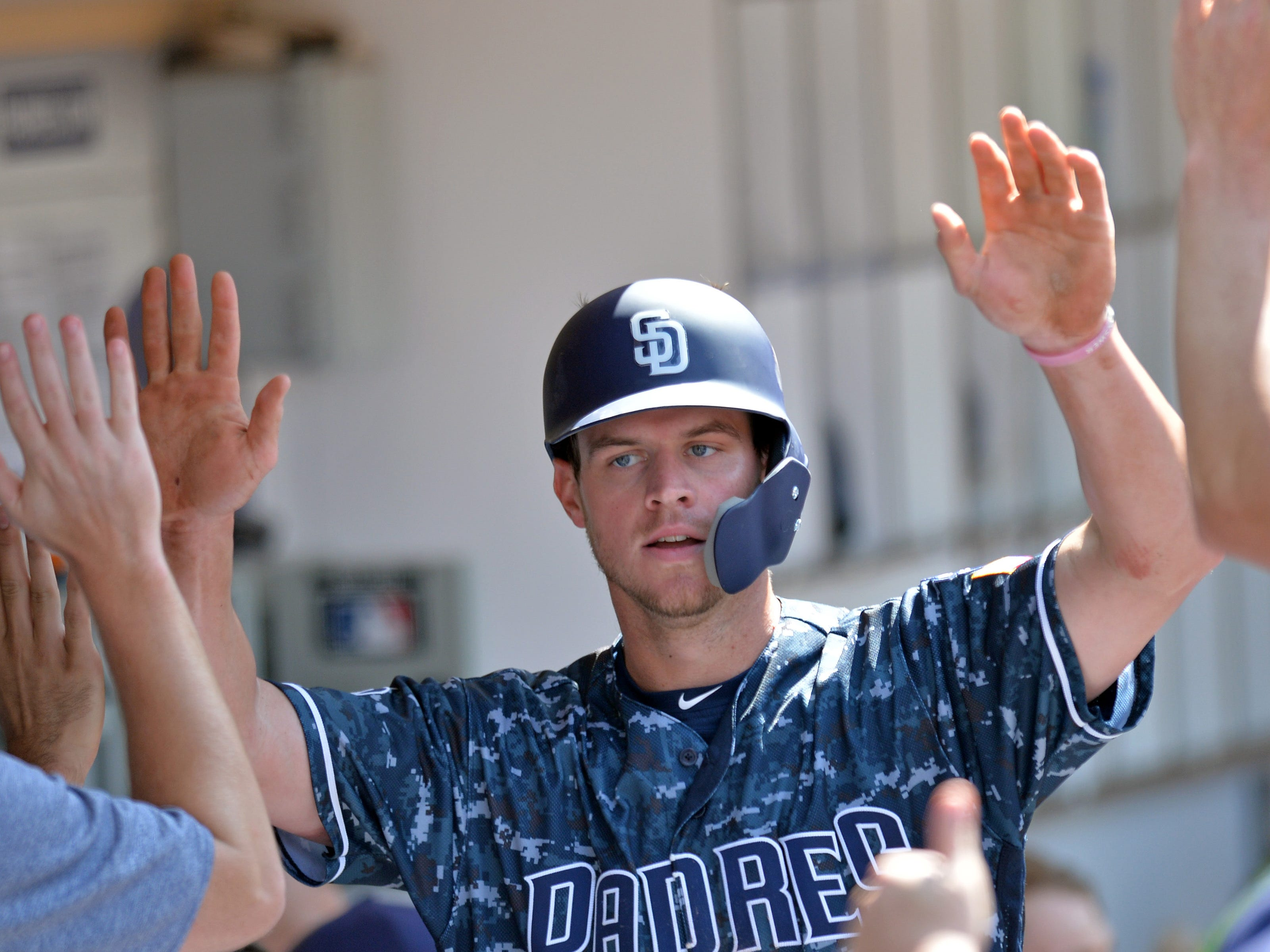 Aug 19, 2018; San Diego, CA, USA; San Diego Padres third baseman Wil Myers (4) is congratulated after scoring in the sixth inning against the Arizona Diamondbacks at Petco Park. Mandatory Credit: Jake Roth-USA TODAY Sports