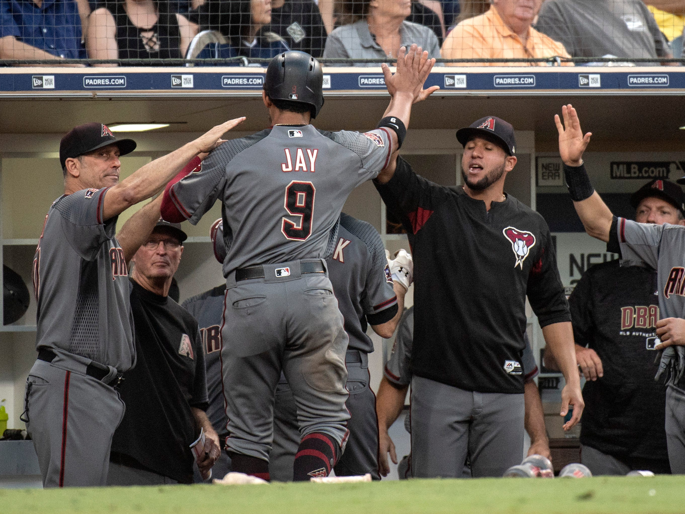 Arizona Diamondbacks' Jon Jay (9) is welcomed in the dugout after scoring on a sacrifice fly by A.J. Pollock during the fifth inning of a baseball game against the San Diego Padres in San Diego, Saturday, Aug. 18, 2018. (AP Photo/Kyusung Gong)