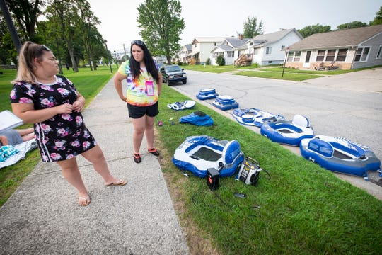 Mikalyn Ribonson, left, of Auburn Hills, and Cyndi Foote, of Sandusky, talk while inflating a number of flotation devices for their group before the annual Float Down Sunday, Aug. 19, 2018, at Lighthouse Beach.