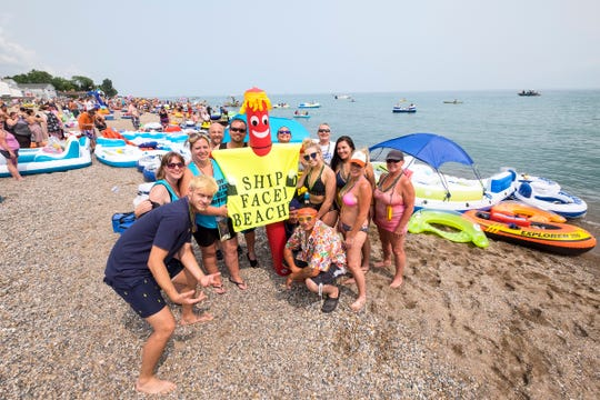 Several of the Ship Faced Beaches, a group of about 25 Float Down participants, pose for a photo near their rafts Sunday, Aug. 19, 2018, before the launch of the annual Float Down at Lighthouse Beach.