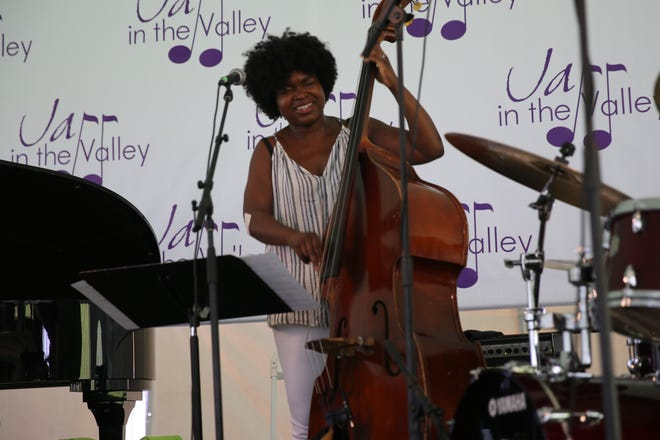 Mimi Jones, of the jazz band The Black Madonna, smiles as she plays the upright bass on Sunday in Victor C. Waryas Park. She has performed with artists such as Beyonce and Frank Ocean.