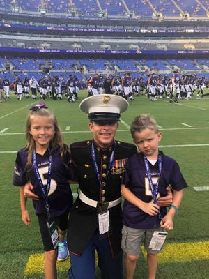 Kodi Bowers, 32, Greencastle, poses for a photo with his two children on the field during a home game for the Baltimore Ravens the evening of Aug. 9 in Baltimore, Md. Bowers was honored as a Hometown Hero by the football team for his service in the U.S. Marine Corps.