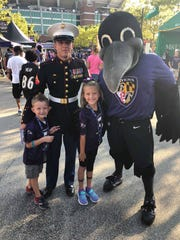 Kodi Bowers, 32, Greencastle, poses for a photo with his two children and the Baltimore Ravens' mascot during a home game the evening of Aug. 9 in Baltimore, Md. Bowers was honored as a Hometown Hero by the football team for his service in the U.S. Marine Corps.