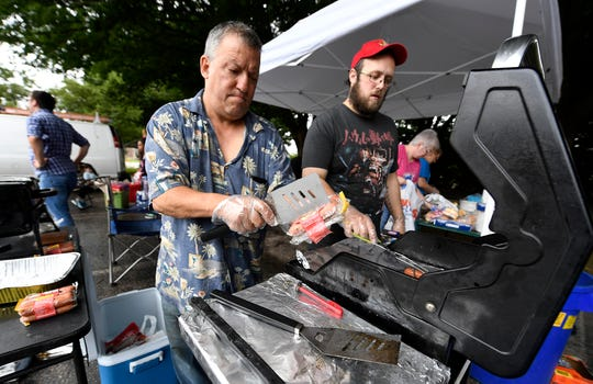 York Giving Helping Hands volunteers Michael Gurreri, left of Spring Garden, and Alex Jones of Lewsiberry, grill hotdogs for York's homeless and under-privileged along the Rail Trail in the city, Sunday, August 18,  2018. John A. Pavoncello photo