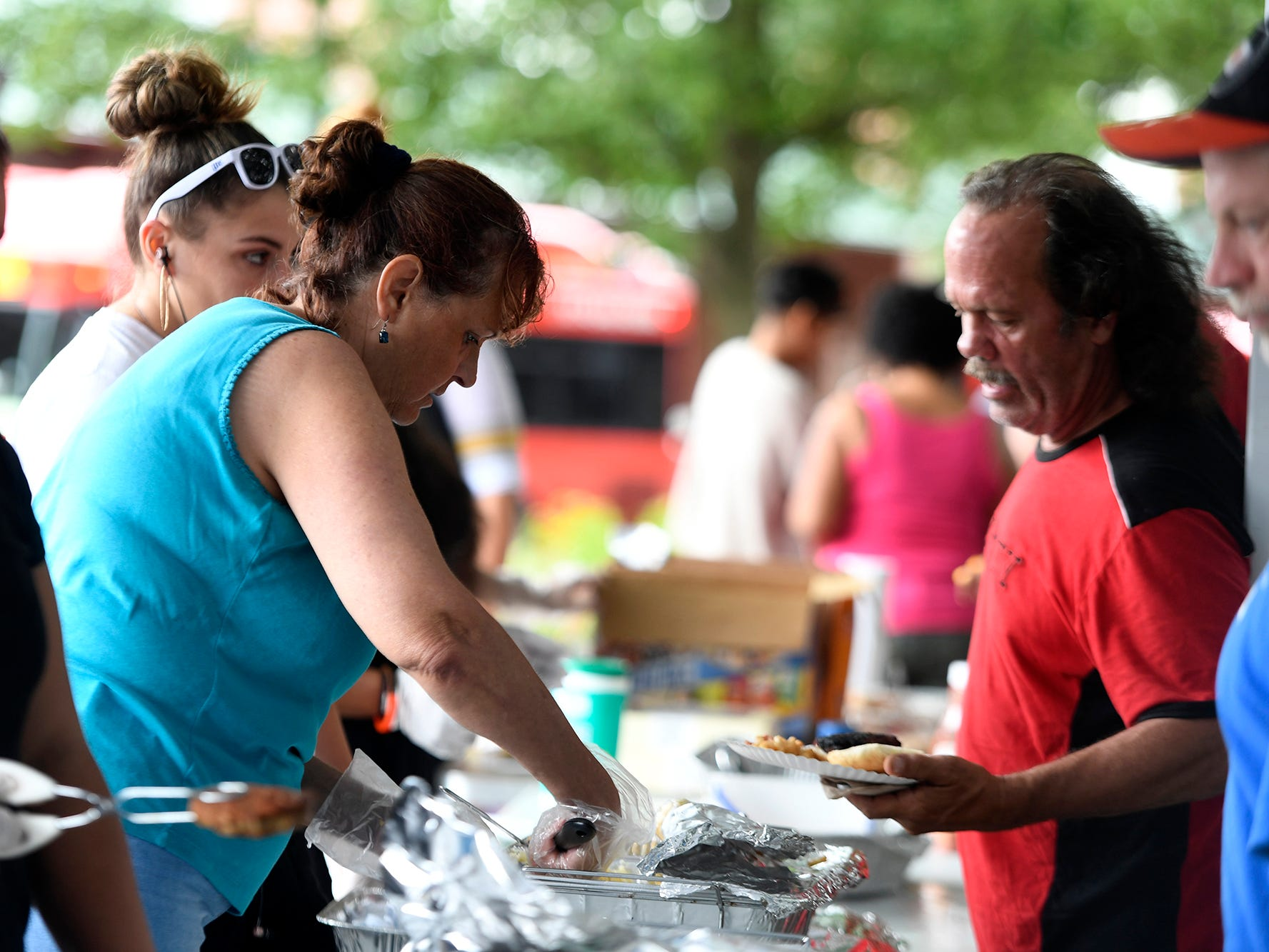 Volunteers with York Giving Helping Hands provide a meal for York's homeless and under-privileged along the Rail Trail in the city, Sunday, August 18,  2018. John A. Pavoncello photo