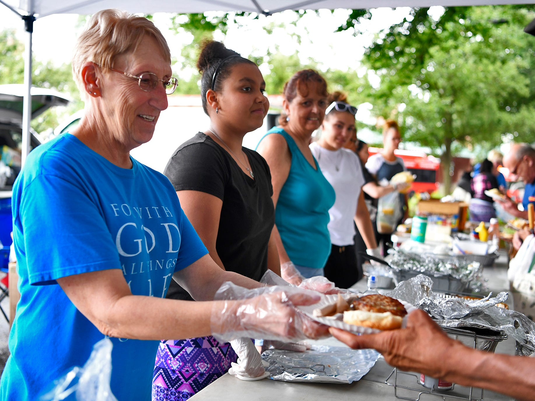 York Giving Helping Hands Volunteers  Tina Sweeley, left, Alysia Moore, both of York, Kathy Arnold of Manchester and Sierra Sauble of North York, right, dish up meals for York's homeless and under-privileged along the Rail Trail in the city, Sunday, August 18,  2018. John A. Pavoncello photo