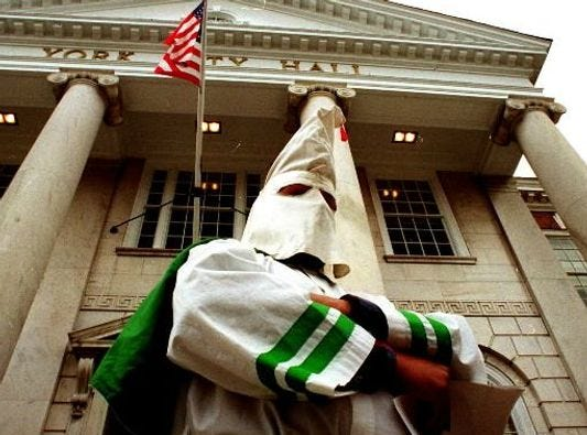A Klansman stands on the steps of York City Hall in the mid 1990s. That appearance wasn't the first or last time the Ku Klux Klan has emerged in public view. In the 1920s, the Klan, a force after the Civil War, reformed in York County, as elswehere. At a Klonkave in North York in 1929, for example, North York's chief burgess, council members and playground association members rode in two cars leading a Klan parade. Five hundred marchers in full uniform followed. More about the Klan's presence in York County's story follows ... . - Jim McClure