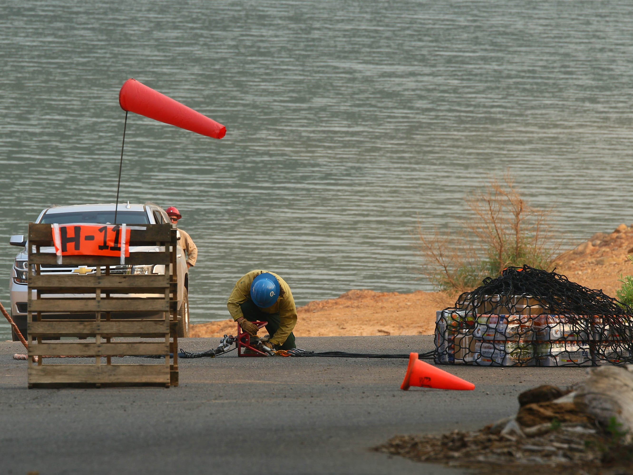 A fire crew on Saturday, Aug. 18, 2018 hooks up a net containing supplies for the pilots operating the helicopters at near the Hirz Bay boat ramp. (Special to the Record Searchlight/Hung T. Vu)