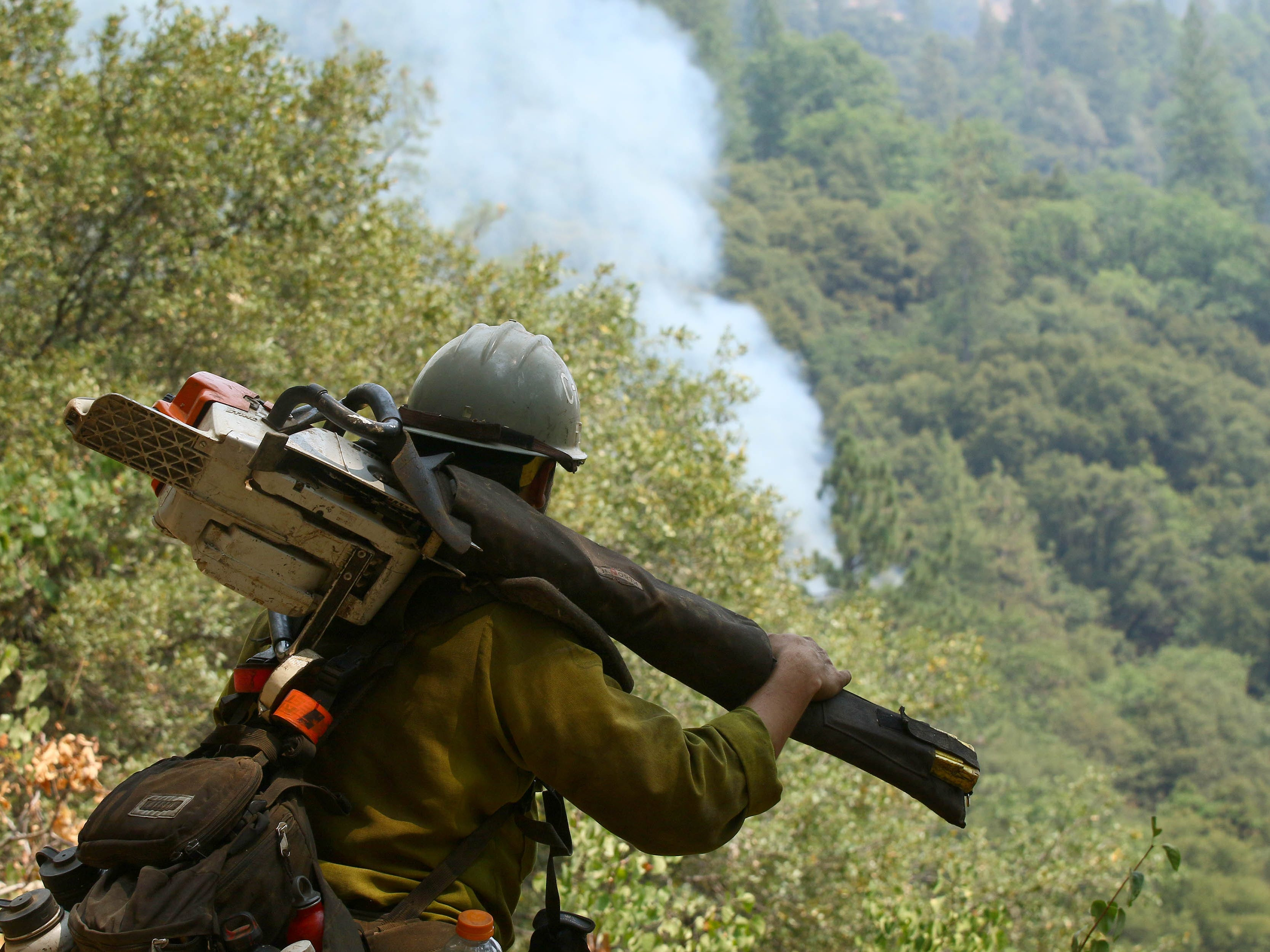 Dane Bjerklie with the U.S Forest Service's Type II Initial Attack crew, watches as the smoke rises on the ridge near Bollibokka along the McCloud River by Gillman Road on Saturday, Aug. 18, 2018. (Special to the Record Searchlight photo by Hung T. Vu)