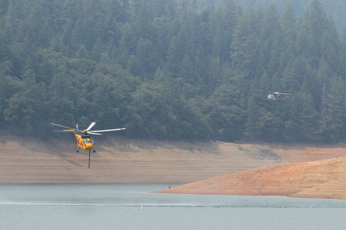 In the northeast section by Bollibokka Club along McCloud River on Saturday, Aug. 18, 2018 a helicopter drops water on a hot spot on the ridge. Helicopters have been collecting water from Lake Shasta at Hirz Bay area to drop on the fire. (Special to the Record Searchlight photo by Hung T. Vu)