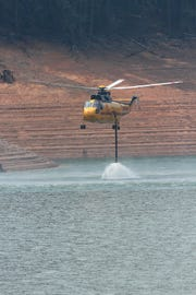 A Helicopter fills up with water from Lake Shasta at Hirz Bay to fight the fire on Saturday, Aug. 18, 2018. (Special to the Record Searchlight photo by Hung T. Vu)