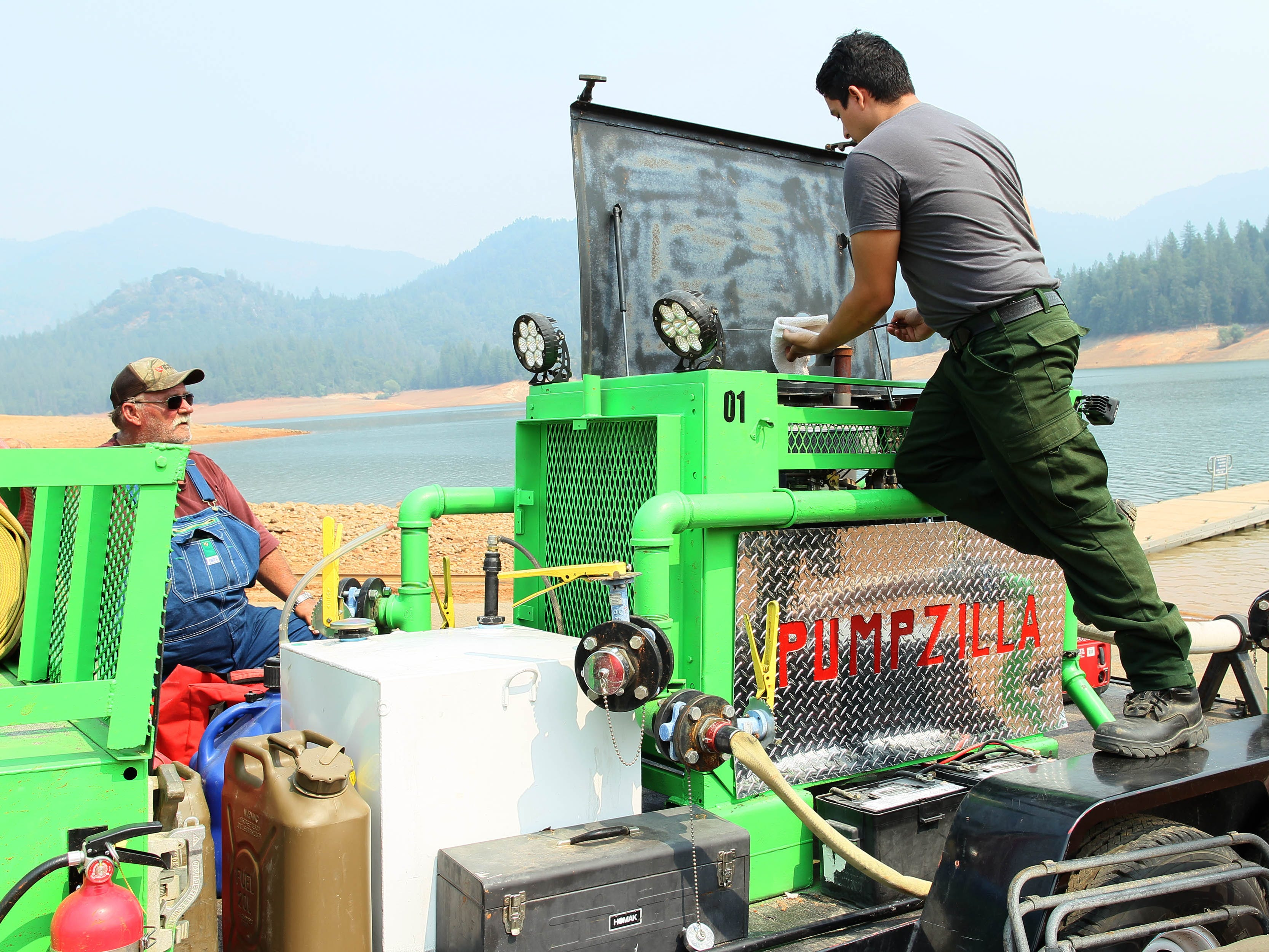 Jesse Lea, left, and Abel Pini, both are operators of the Pumpzilla Fire Support. They check the oil on the pump before refilling water for the tankers at Hirz Bay on Saturday, Aug. 18, 2018. (Special to the Record Searchlight/Hung T. Vu)