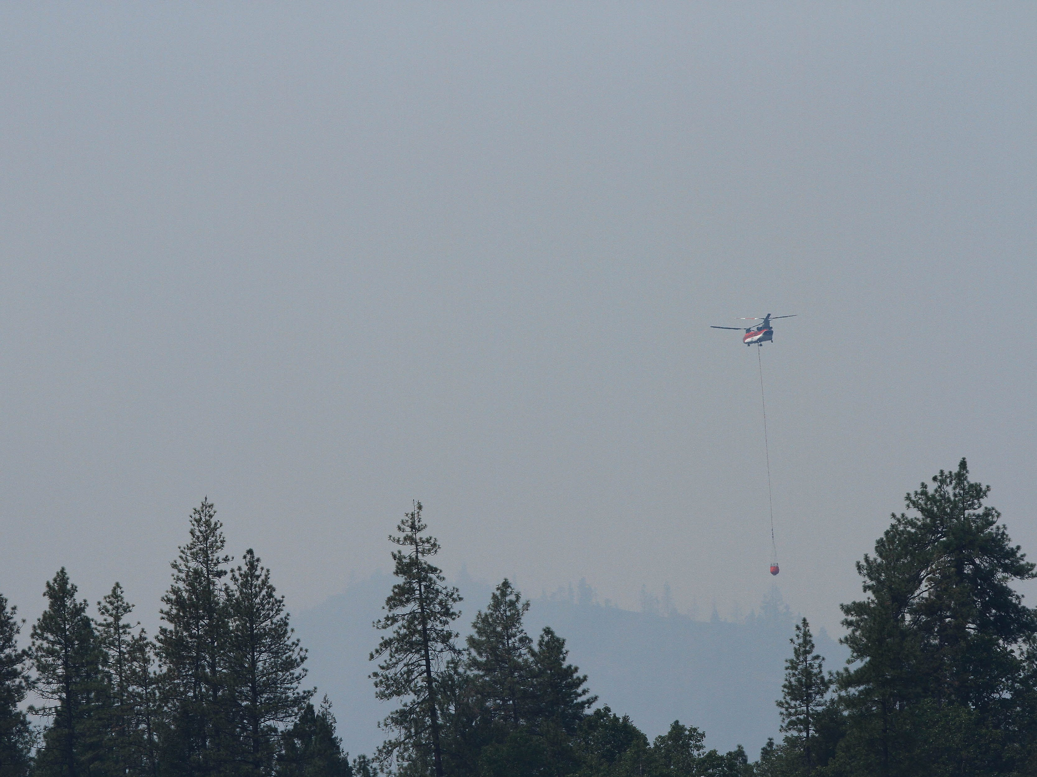 In the northeast section by Bollibokka Club along McCloud River on Saturday, Aug. 18, 2018 a helicopter drops water on a hot spot on the ridge. Helicopters have been collecting water from Lake Shasta at Hirz Bay area to drop on the fire. (Special to the Record Searchlight/Hung T. Vu)