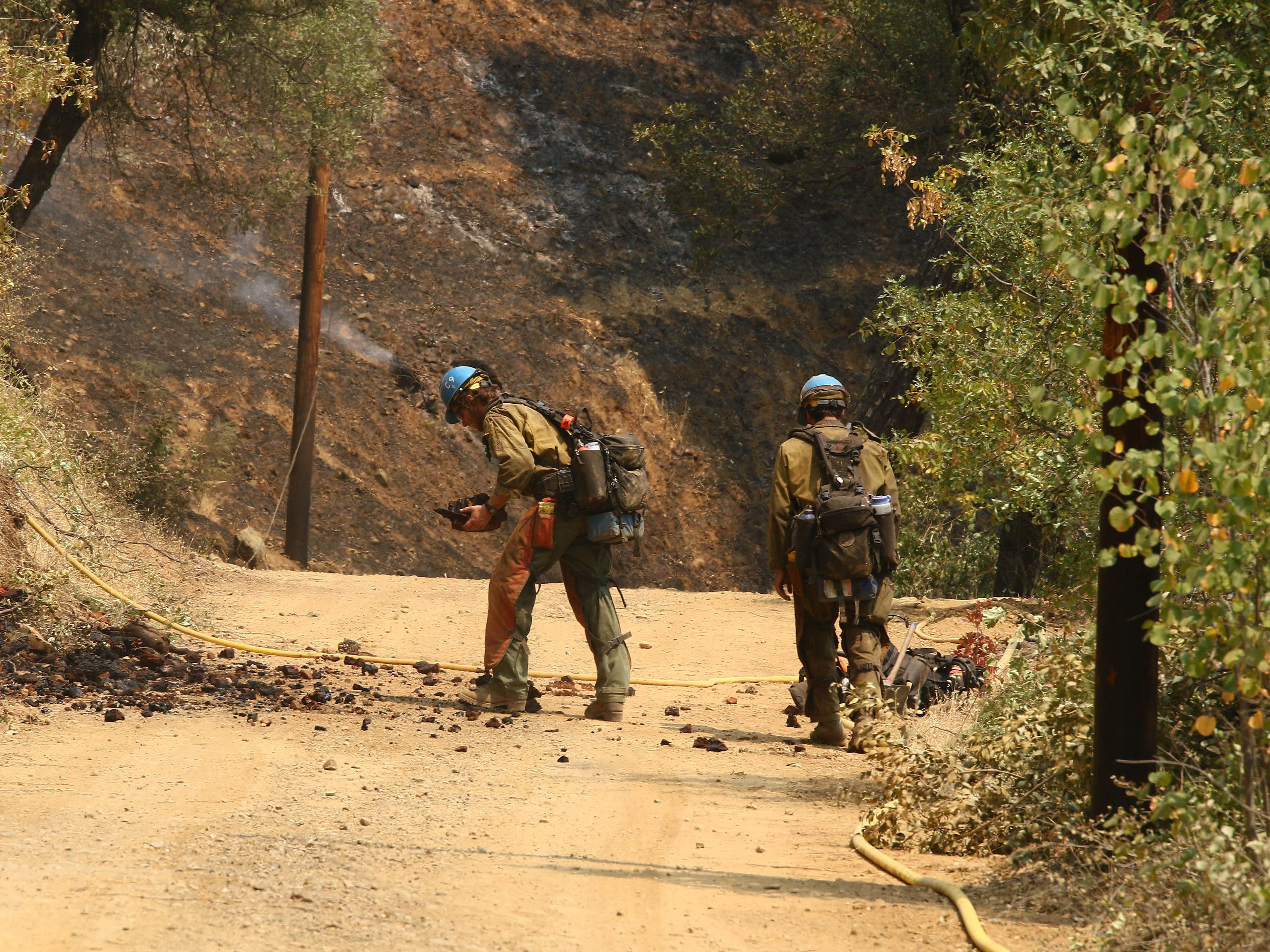 A hotshot crew picks up some ember on the road near Bollibokka Club along the McCloud River on Saturday, Aug. 18, 2018 at the Hirz Fire. (Special to the Record Searchlight/Hung T. Vu)
